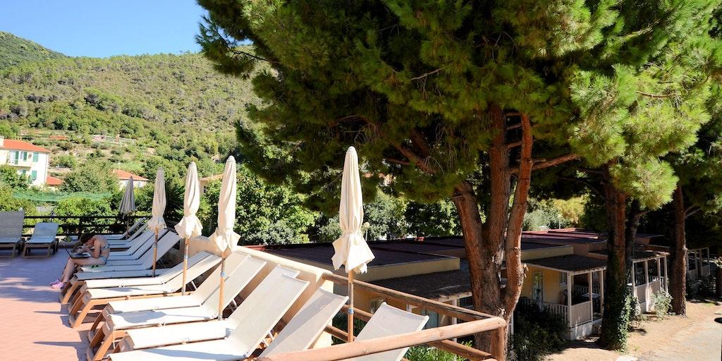 Hier sehen Sie die Terrasse am Pool und im Hintergrund die Bungalow-Reihenhäuser Villino