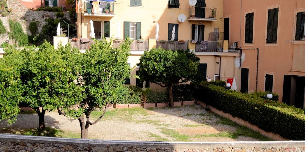 Die Wohnungen mit eigener Terrasse sind hinter der Hecke (auf der rechten Seite)