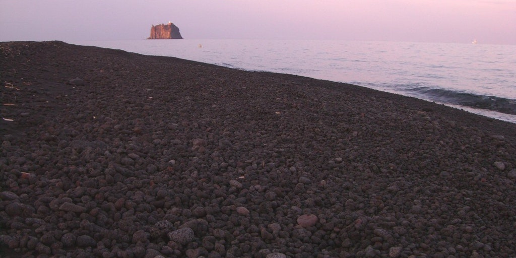 Strombolicchio in evening twilight seen from Stromboli's black beach