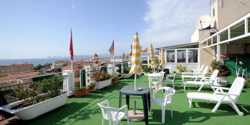 The roof terrace with sun loungers and semi-covered breakfast terrace