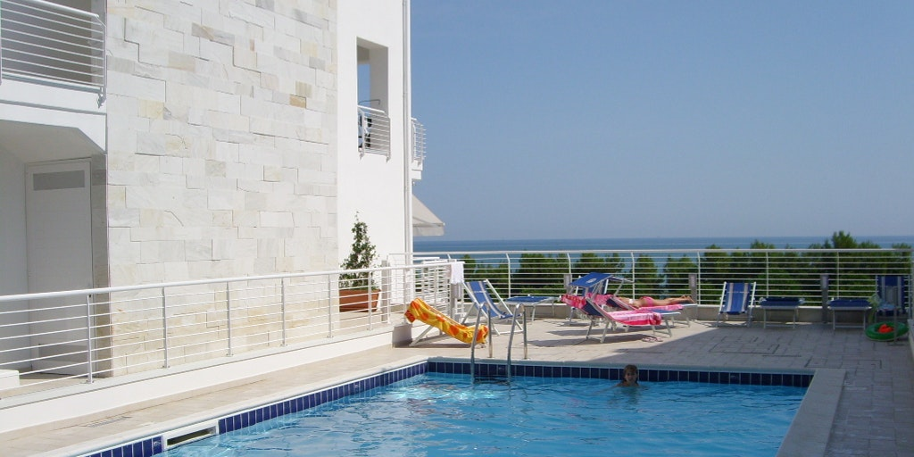The communal swimming pool with views from the ground floor in the background