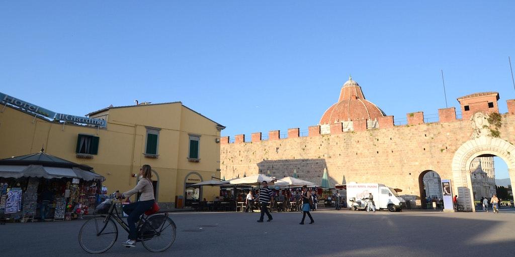 Hotellet till vänster och Det Lutande Tornet ses genom porten till höger